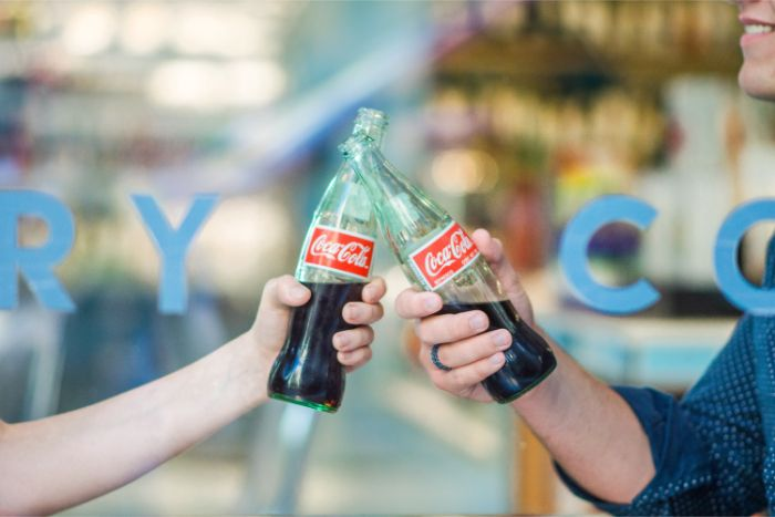person holding Coca-Cola bottle