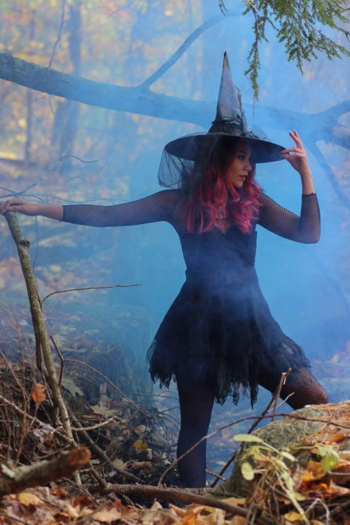 woman-in-black-witch-costume-standing-beside-rock